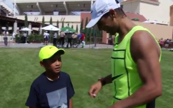 Nadal gives young boy a football lesson, and signs his hat
